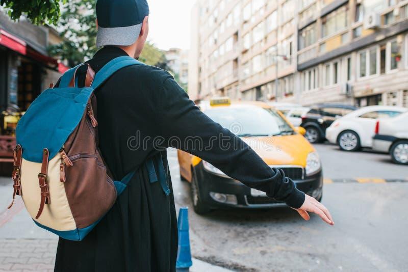 Den unga manliga turisten med en ryggsäck i storstaden väntar på en taxi resa Sight Resor royaltyfri bild