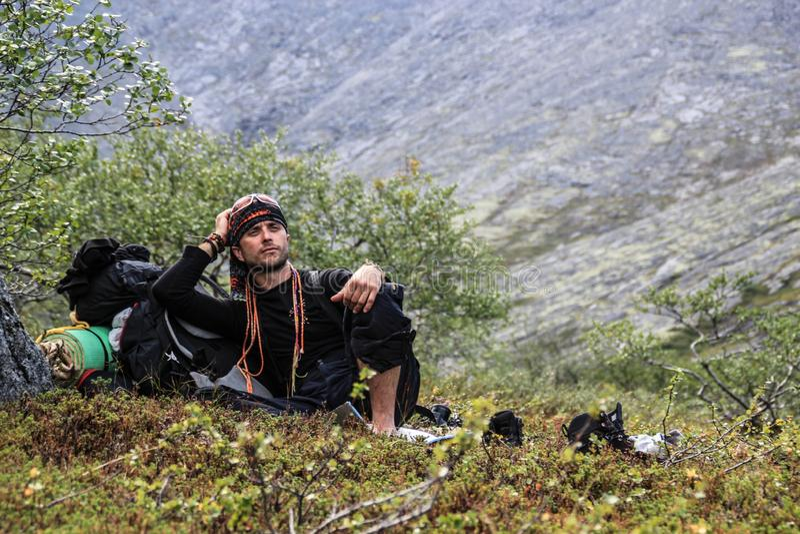 Den unga manliga turisten satt ner för att vila i en bergvandring arkivfoto