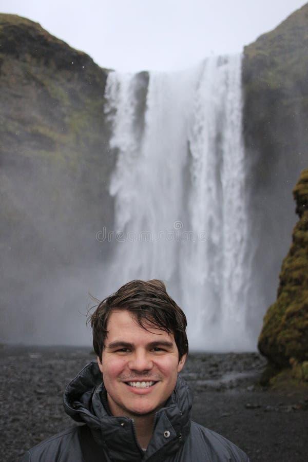 Den unga manliga turisten som åldras 20-25, poserar framme av skogafossvattenfallet i Island Island har blivit en populär turist royaltyfria bilder