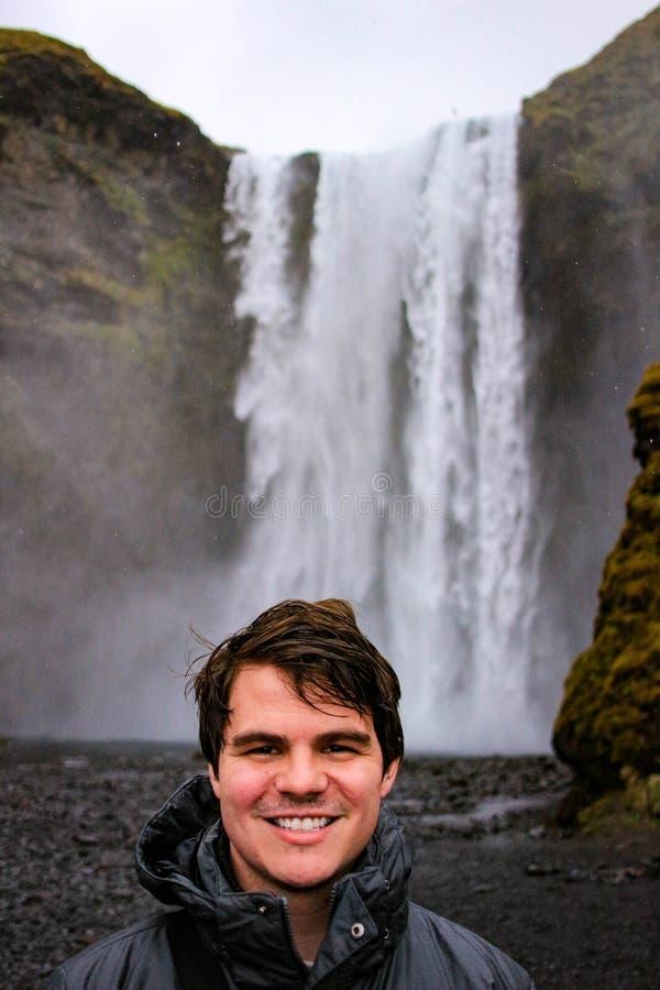 Den unga manliga turisten som åldras 20-25, poserar framme av skogafosswaterf royaltyfria bilder