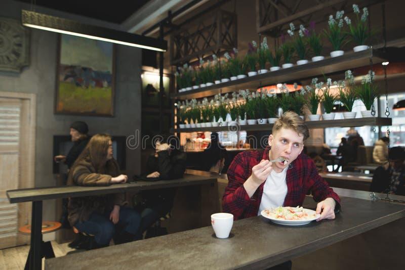 den unga mannen äter en sallad i en hemtrevlig restaurang Det studentdisken och kaffet i kafét arkivbilder