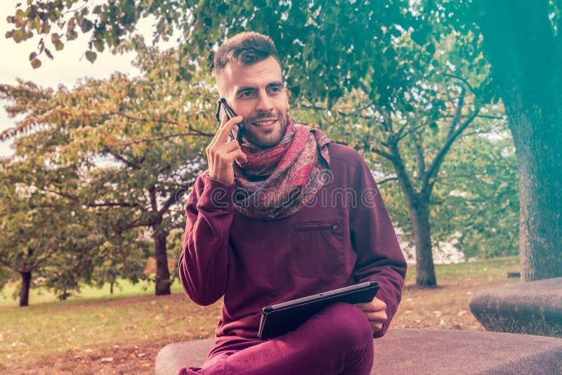 Den unga mannen arbetar på minnestavladatoren, medan tala på telefonen, utomhus gör mellanslag offentligt parkerar nära fotografering för bildbyråer