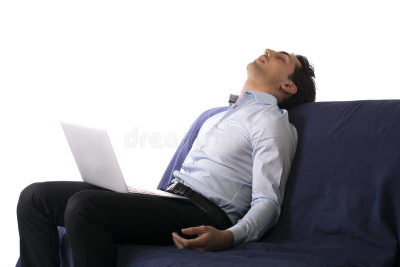 Den unga mannen avverkar sovande på vitt arbete för soffan på bärbar datordatoren arkivfoton