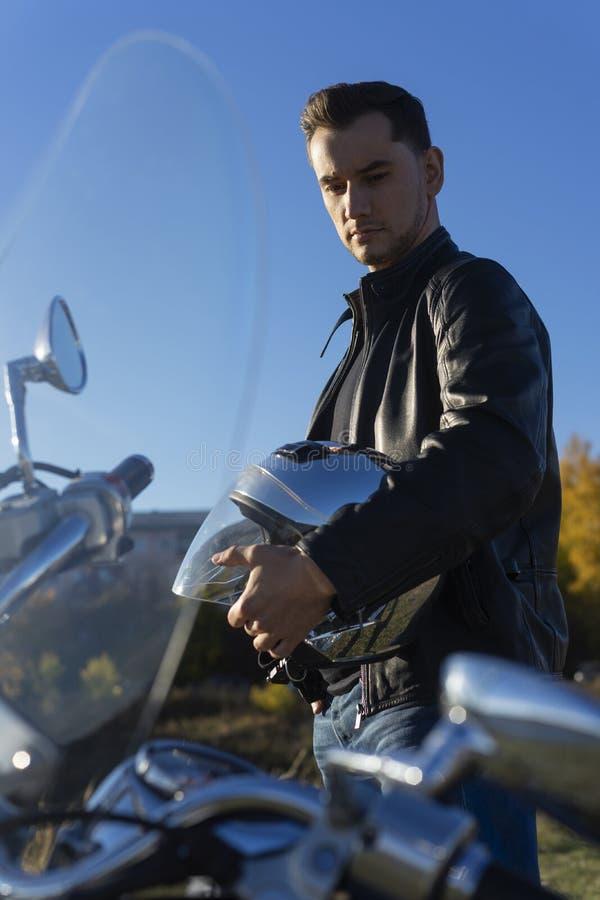 Den unga mannen bärande svarta håll för ett läderomslag avspeglar hjälmen in arkivbilder