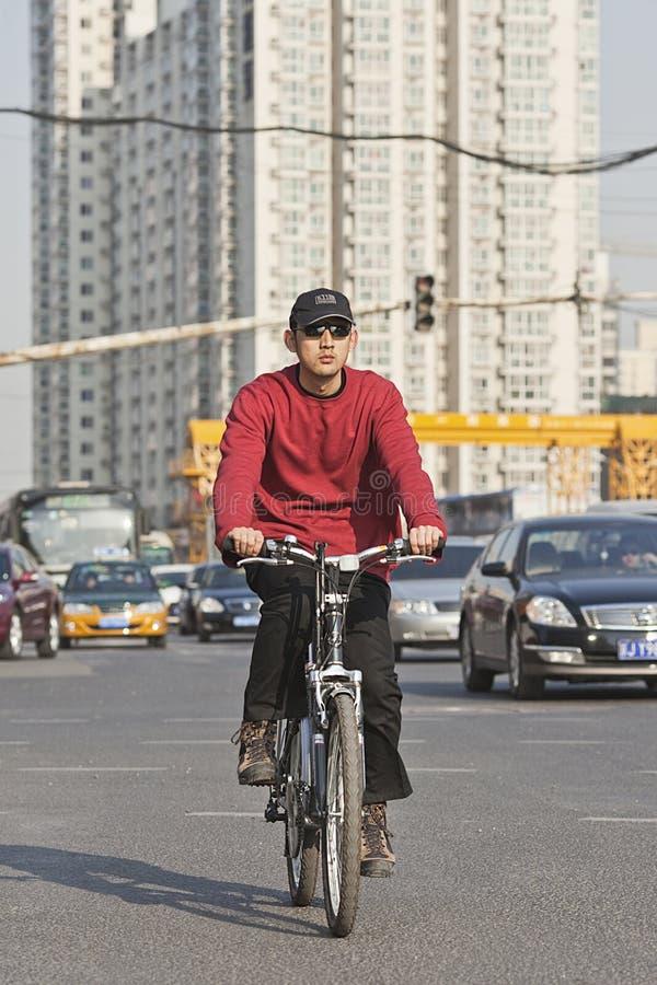 Den unga mannen cyklar i Pekingmitt med hyreshusar på bakcground, Kina arkivbilder