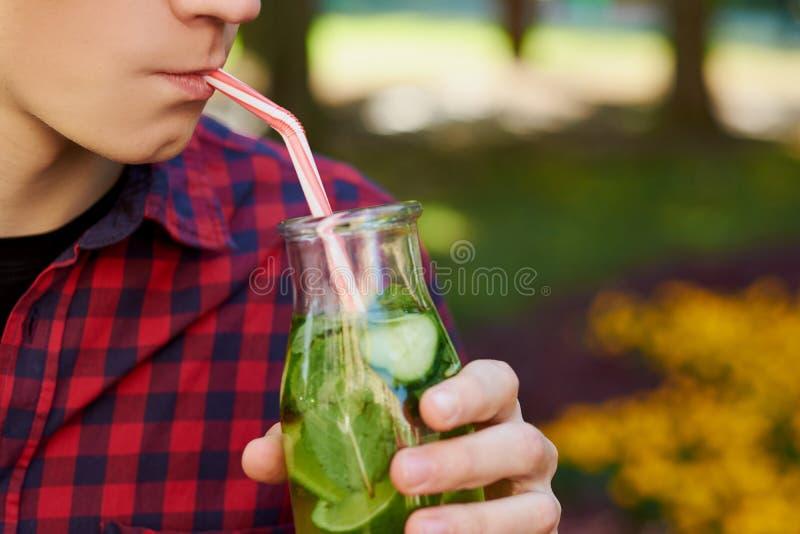 Den unga mannen dricker sunt detoxte royaltyfri fotografi