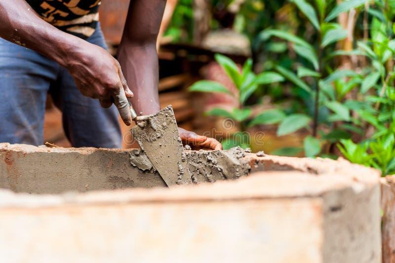 Den unga mannen för den svarta afrikanen räcker arbete med cement för att bygga vatten väl i den africa byn royaltyfri foto