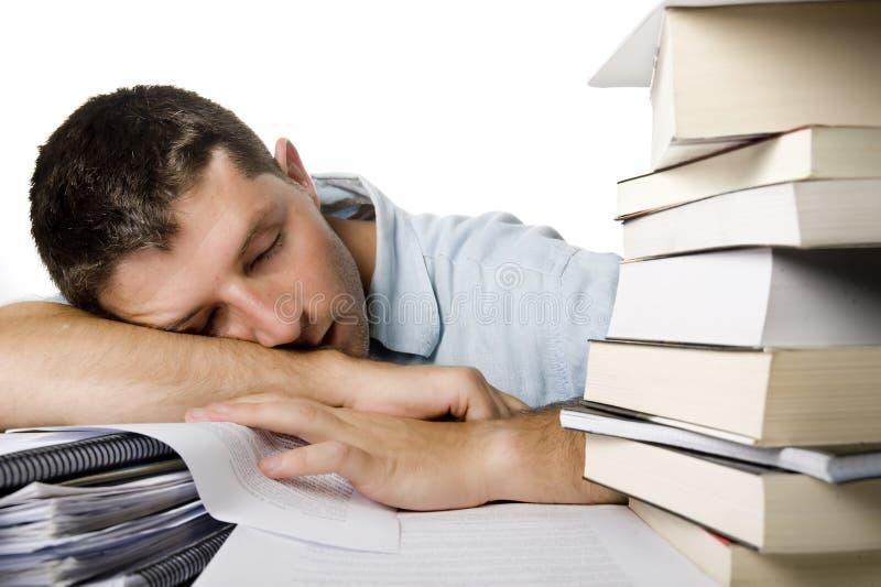 Den unga mannen förkrossade att sova över en hög av böcker royaltyfria foton