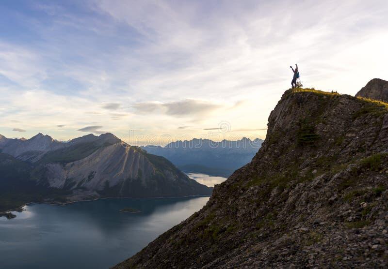Den unga mannen firar nå maximumet av ett berg royaltyfria foton