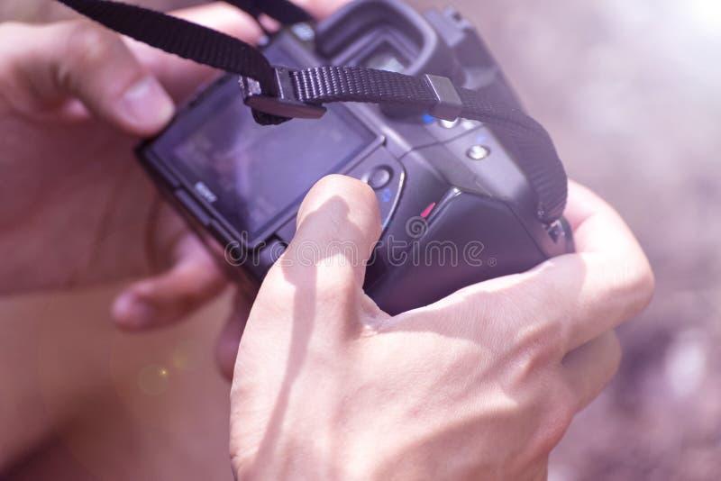 Den unga mannen går i skogen med kameran royaltyfria bilder