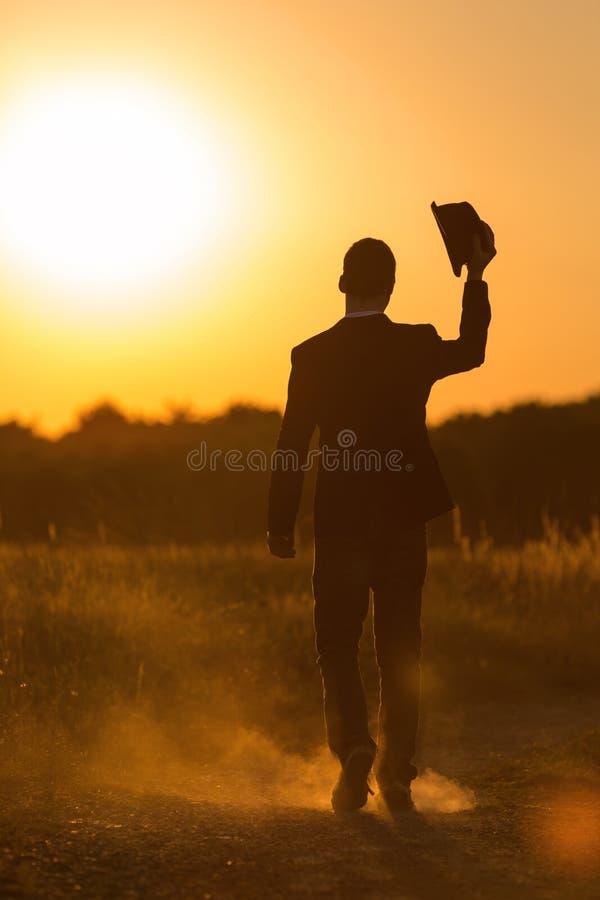 Den unga mannen går i solnedgång 2 fotografering för bildbyråer