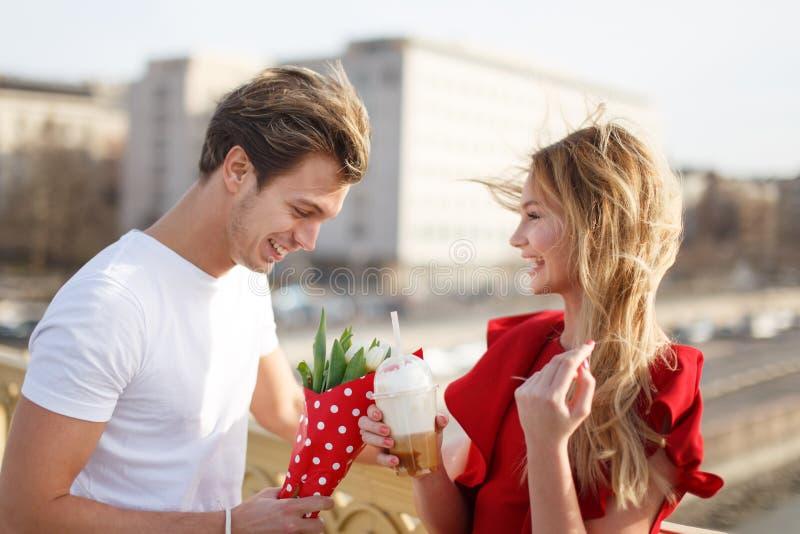 Den unga mannen ger buketten till kvinnan i rött datum för klänning först arkivbild