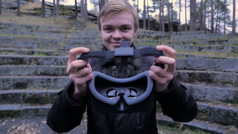Den unga mannen ger en virtuell verklighethörlurar med mikrofon i parkera Den unga mannen ger en virtuell verklighethörlurar med  royaltyfri fotografi