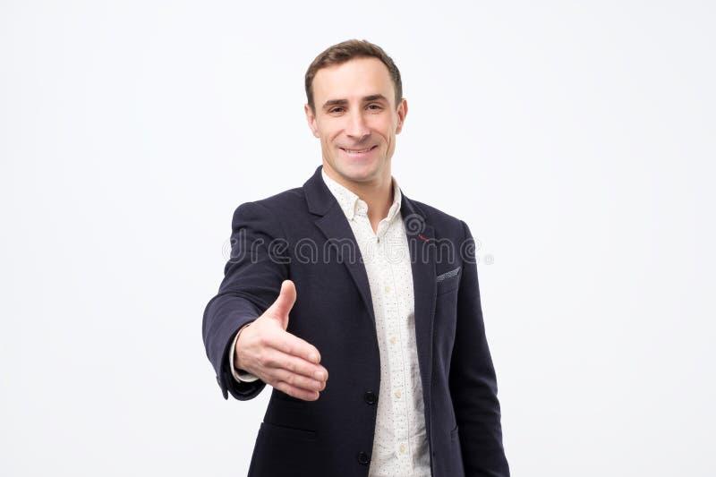 Den unga mannen ger handskakningen, hälsar med någon, jublar möte royaltyfria foton