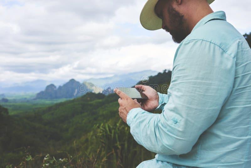 Den unga mannen håller ögonen på videoen som honom åtog sigcelltelefonen av en härlig djungelsikt arkivbilder