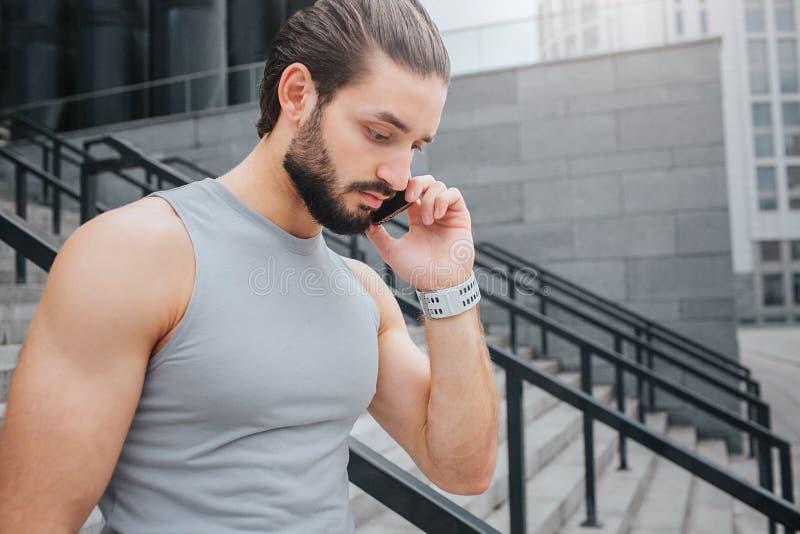 Den unga mannen i bra form går ner moment Han talar på telefonen Grabben koncentreras Han ser ner Den unga mannen har handband fotografering för bildbyråer