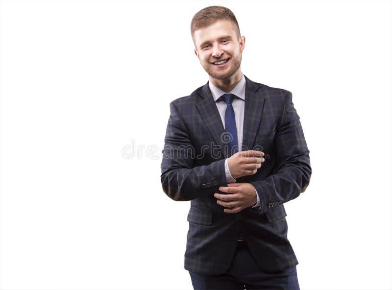 Den unga mannen i dräkt justerar hans manschetter royaltyfria foton