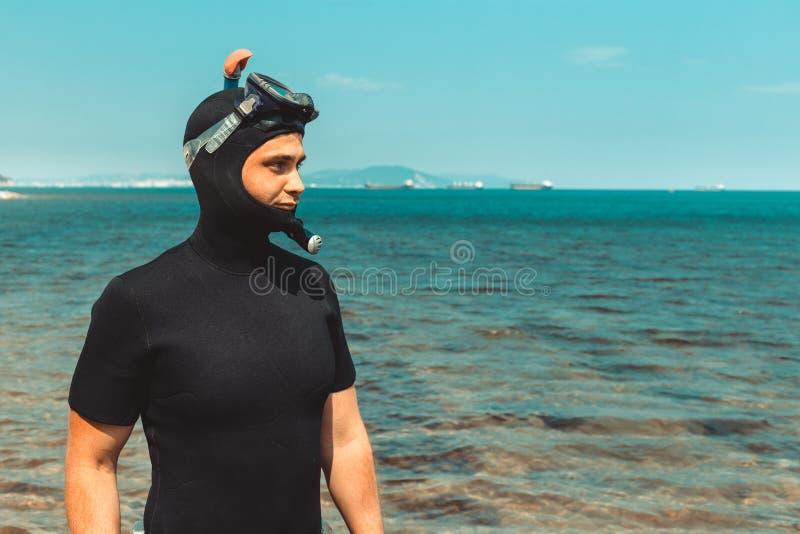 Den unga mannen i dykningdräkt går till havet i sommar utomhus arkivfoto