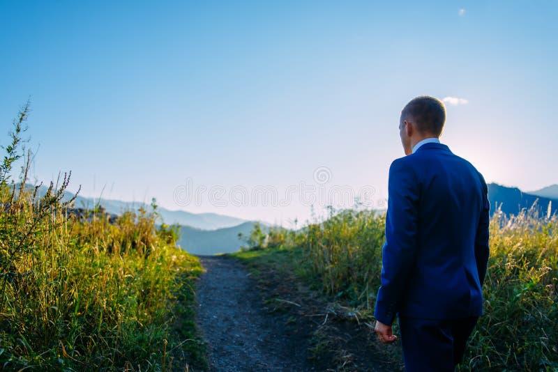 Den unga mannen i en aff?rsdr?kt p? bakgrunden av berg g?r till hans syfte p? en solig sommardag arkivfoto