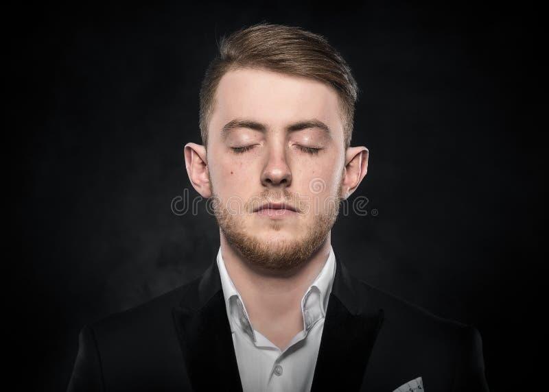 Den unga mannen i en dräkt sover arkivfoto