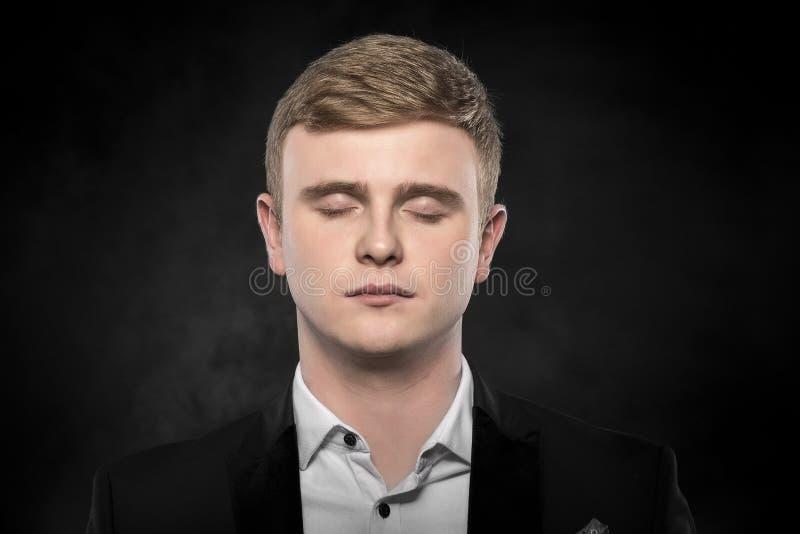 Den unga mannen i en dräkt sover royaltyfri foto
