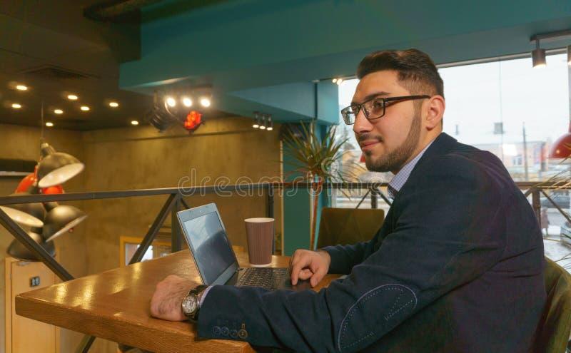 Den unga mannen i exponeringsglasstudier handlar diagram på en bärbar dator, medan sitta i ett kafé royaltyfri bild