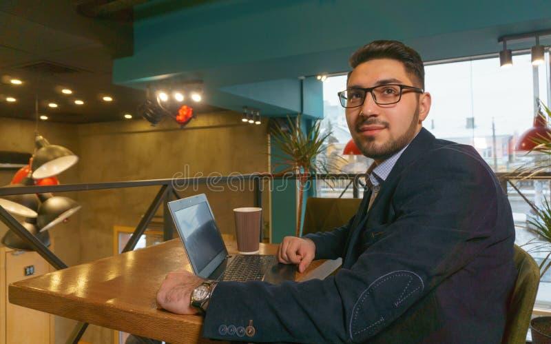 Den unga mannen i exponeringsglasstudier handlar diagram på en bärbar dator, medan sitta i ett kafé royaltyfria bilder