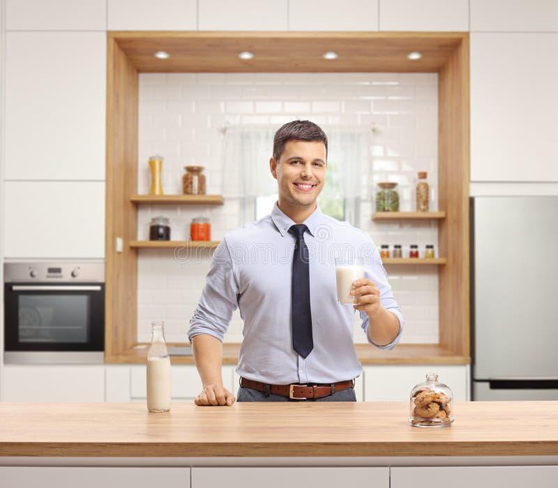 Den unga mannen i formell kläder som rymmer ett exponeringsglas av, mjölkar och anseendet i ett modernt kök royaltyfria bilder