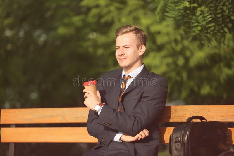 Den unga mannen i formell kläder som vilar med koppen kaffe i, parkerar på solig dag arkivfoton