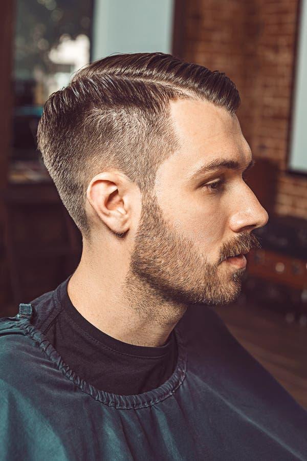 Den unga mannen i frisersalong fotografering för bildbyråer