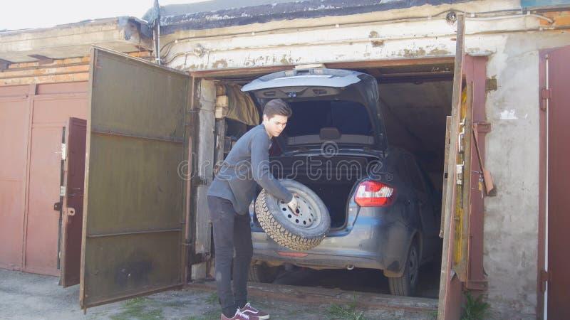 Den unga mannen i handskar lastar av hjulet från bilstammen i garage arkivfoton