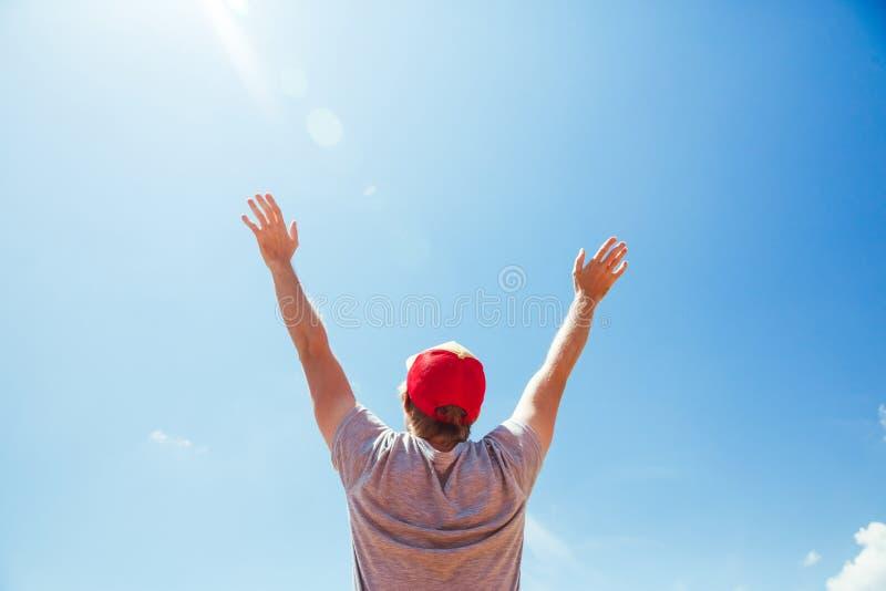 Den unga mannen i hatt som tycker om sommartid, lyftte händer reser gå för turist för blå himmel för lyckliga sinnesrörelser för  royaltyfri foto