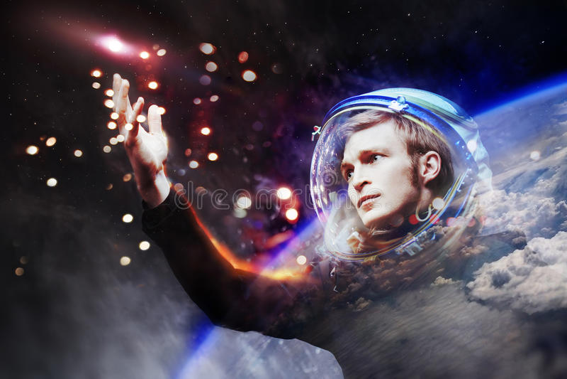 Den unga mannen i imaginär utrymmedräkt sträcker en hand till stjärnorna Tryck på stjärnorna Begreppet av utforskning av rymden royaltyfri fotografi