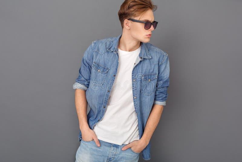 Den unga mannen i jeans klår upp och solglasögonstudion som isoleras på grå färger som åt sidan coolt ser fotografering för bildbyråer