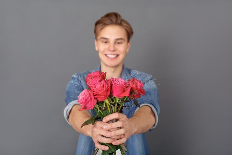 Den unga mannen i jeans klår upp studion på grått berömbegrepp med suddig bakgrund för rosnärbilden fotografering för bildbyråer