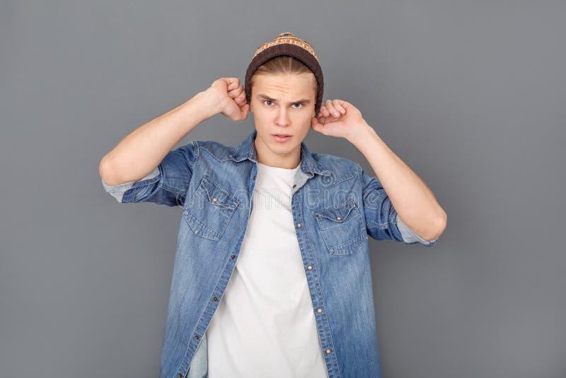 Den unga mannen i jeans klår upp studion som isoleras på grått stilfullt royaltyfria foton