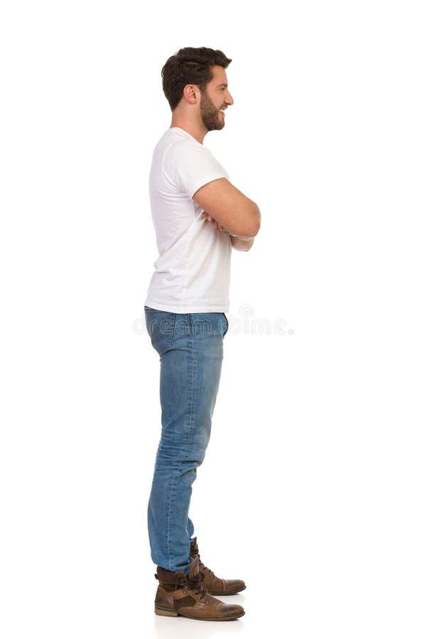Den unga mannen i jeans och den vita T-tröja står med korsade armar och ser bort Slapp fokus royaltyfria foton