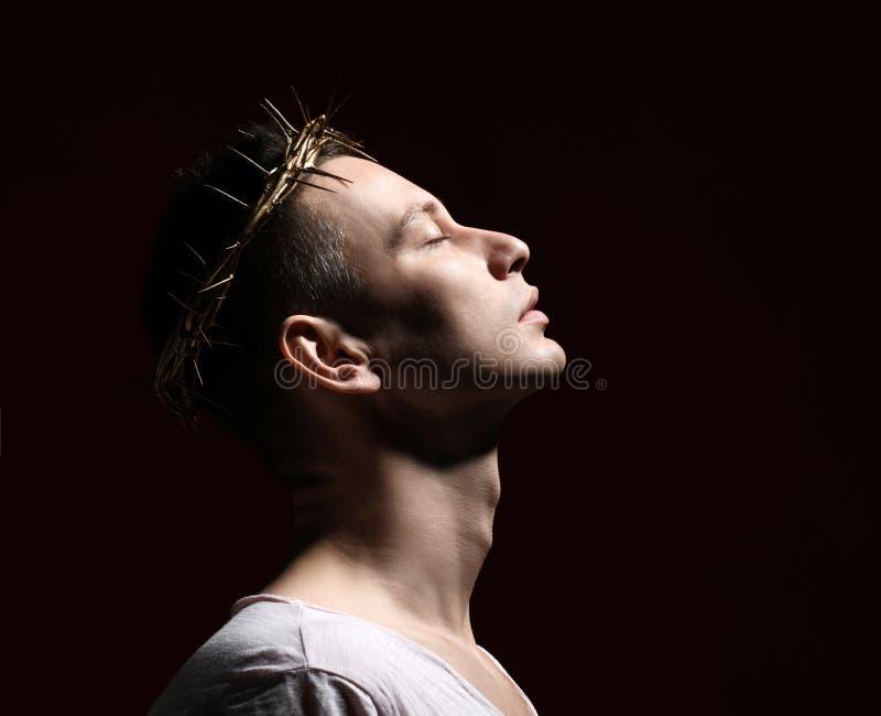 Den unga mannen i krona av taggar, martyren, helgon rymmer hans framsida lyft till himmel skjuten sida fotografering för bildbyråer