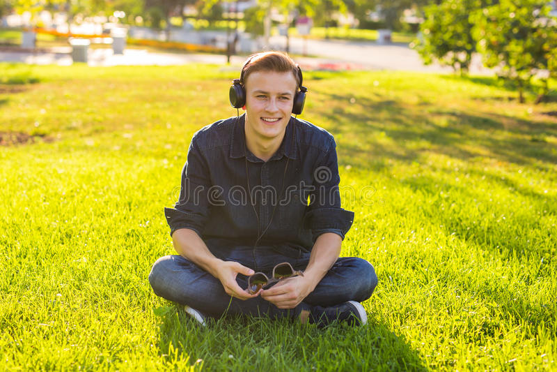 Den unga mannen i parkera lyssnar till musiken arkivfoton