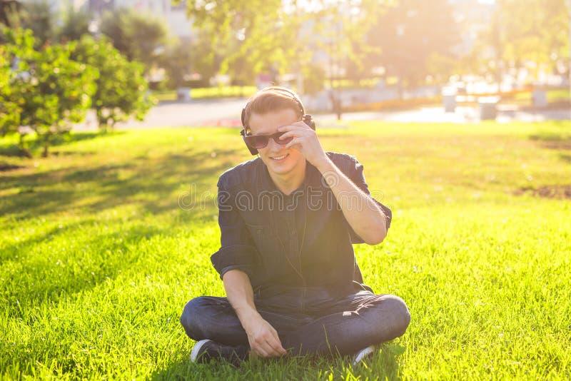 Den unga mannen i parkera lyssnar till musiken arkivbilder