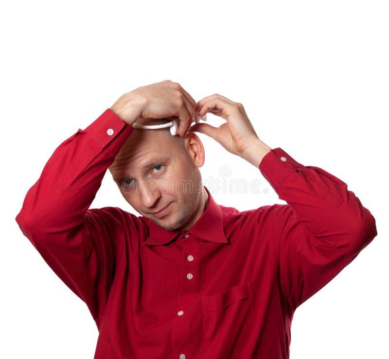 Den unga mannen i röd skjorta sätter på head den electroencephal hörlurar med mikrofonEEG arkivfoto