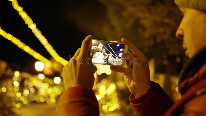 Den unga mannen i rött omslag gör foto med smartphonen i aftonen på julbelysningbakgrund Skjutit p? R?TT arkivfoton