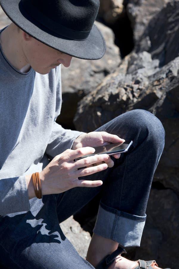 Den unga mannen i svart hatt kontrollerar meddelanden på smartphonen royaltyfri fotografi