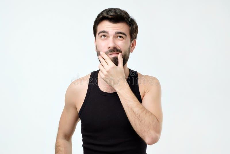 Den unga mannen i svart kläder tänker, ser igenom incredulously, med tvivel arkivfoton