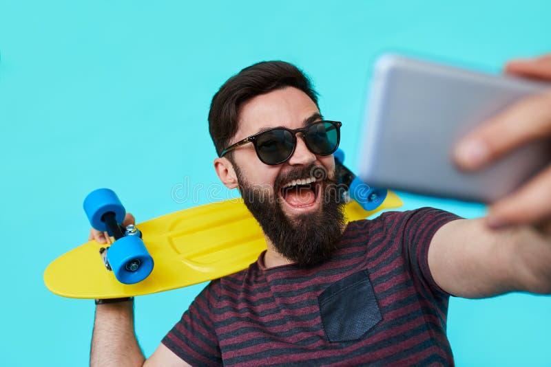 Den unga mannen i tillfällig kläder gör selfie med hans ljusa skateboard royaltyfria bilder