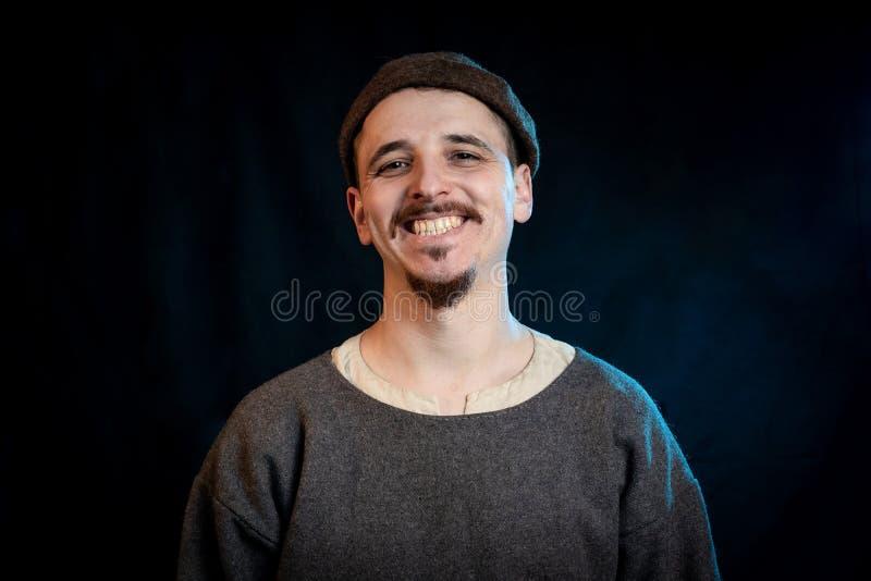 Den unga mannen i tillfällig ullkläder av theearly medeltid som ler, stänger sig upp royaltyfria bilder