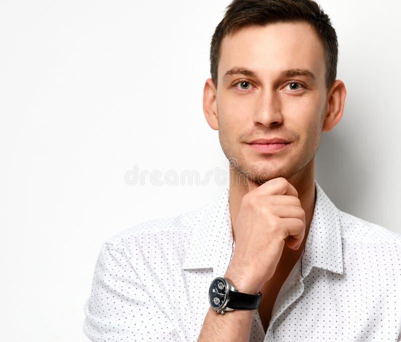 Den unga mannen i den vita tillfälliga skjortan med ett obetydligt leende rymmer hans haka med hans hand på vit arkivfoton