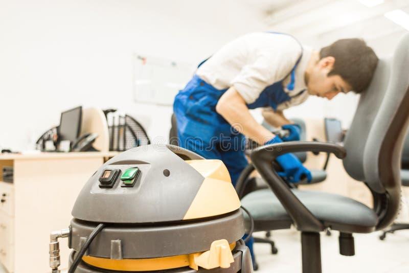 Den unga mannen i workwear- och gummihandskar g?r ren kontorsstolen med yrkesm?ssig utrustning arkivfoton