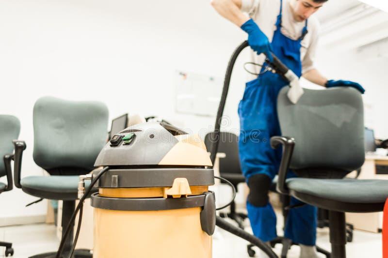 Den unga mannen i workwear- och gummihandskar g?r ren kontorsstolen med yrkesm?ssig utrustning royaltyfri foto