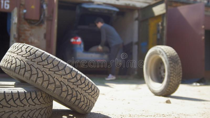 Den unga mannen kastar bort hjulet från hans bilstam arkivfoton